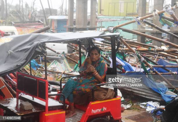 An Indian resident sits on an electric rickshaw next to a damaged structure after Cyclone Fani landfall in Puri in the eastern Indian state of Odisha...