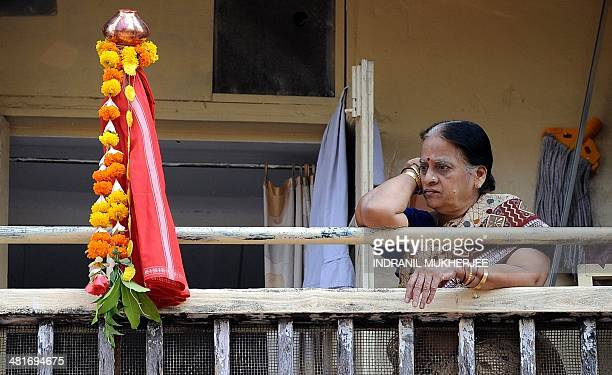 An Indian resident stands next to a 'Gudi' as she watches a procession celebrating 'Gudi Padwa' or the Maharashtrian new year in Mumbai on March 31,...