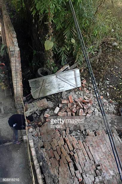 An Indian resident surveys a damaged wall at a house in Imphal on January 4 after a strong 67 magnitude earthquake struck northeast India near the...