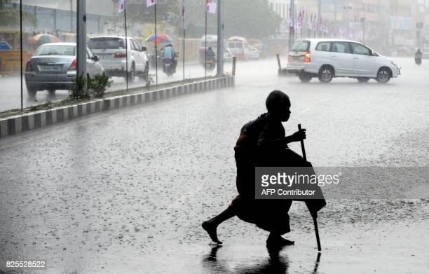 An Indian resident walks across a street during heavy rain in Chennai on August 2 2017 / AFP PHOTO / ARUN SANKAR