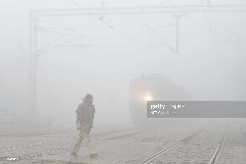 An Indian resident walks over the tracks at a railway crossing amid heavy smog in Amritsar on November 9 2017 Schools closed across large swathes of..