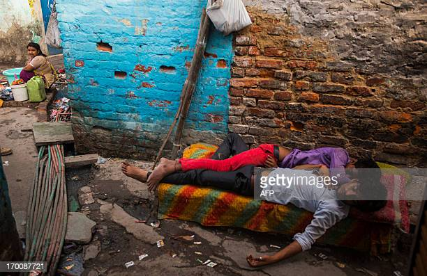 An Indian resident washes clothes near water pipes as two men sleep in a slum area of New Delhi on June 7 2013 India is lagging behind its neighbours...