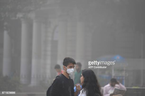 An Indian resident wearing a facemask walks amid heavy smog in New Delhi on November 9 2017 Rickshaw driver Sanjay can only afford a handkerchief to...