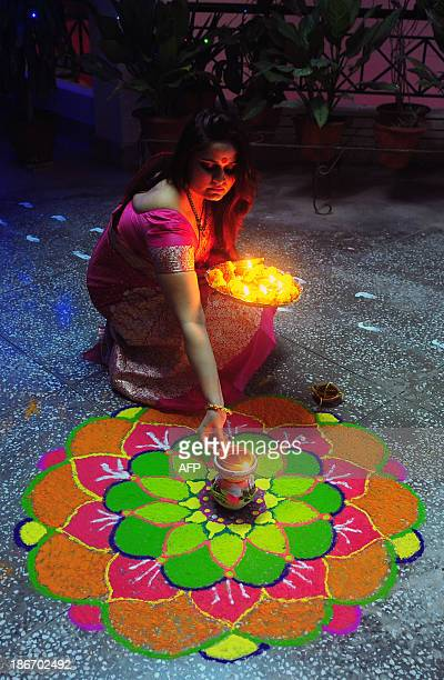 An Indian reveller lights earthen lamps during Diwali celebrations in Allahabad on November 3 2013 Diwali marks the homecoming of the Hindu god Lord...