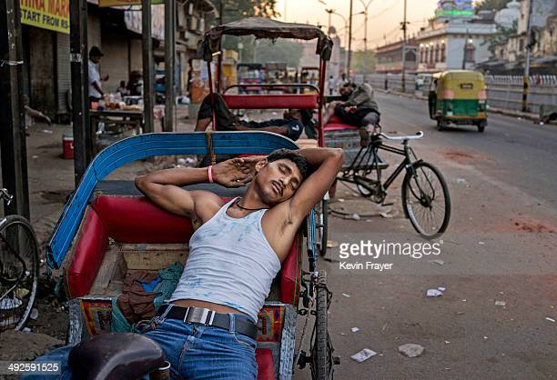 An Indian rickshaw driver naps as he waits for customers on May 21 2014 in Delhi India India elected Hindu nationalist BJP leader Narendra Modi in a...
