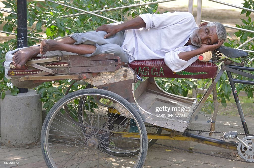 An Indian rickshaw puller sleeps on his rickshaw under the shade of trees on a hot afternoon in Amritsar on June 4 2016 / AFP / NARINDER NANU