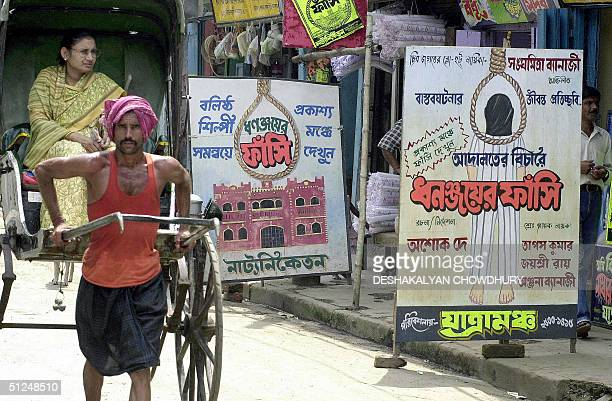 An Indian rickshaw puller takes his passenger past billboards advertising a stage production based on the story of the hanging of Dhananjoy...