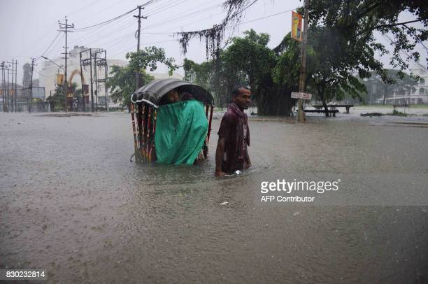 TOPSHOT An Indian rickshaw puller transports a woman through a flooded street during a heavy downpour in Agartala the capital of northeastern state...