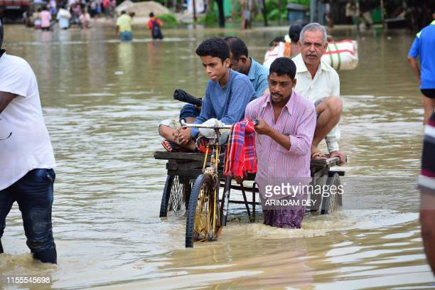 An Indian rickshaw puller transports commuters on a flooded street after a heavy downpour at Baldakhal village in Agartala the capital of...