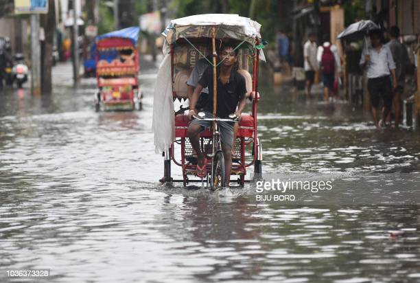 An Indian rickshaw puller transports customers through floodwaters after heavy rains in Guwahati on September 20, 2018.