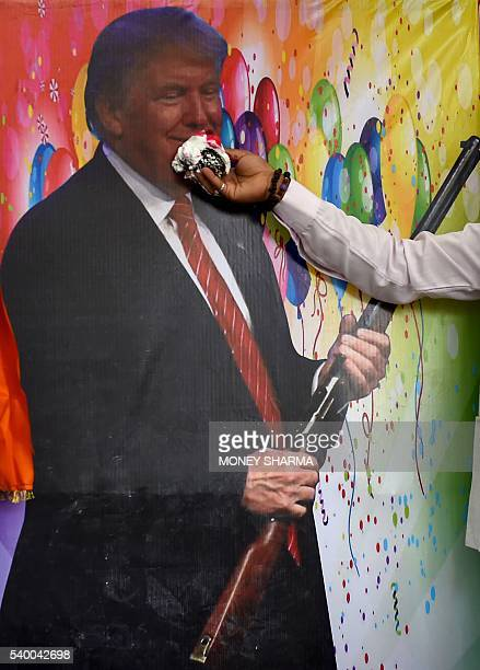 An Indian rightwing Hindu activist holds a piece of cake up against a picture of US Republican presidential candidate Donald Trump during...