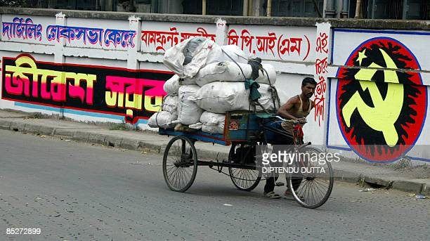 An Indian road rickshaw rider passes by a wall bearing Communist Party of India election slogans in Siliguri on March 6 2009 India's parliamentary...