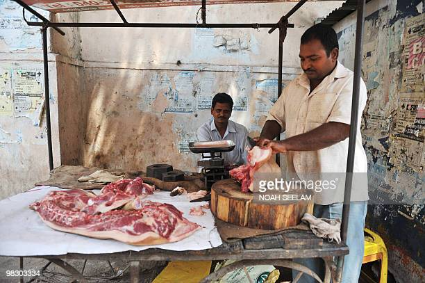 An Indian roadside butcher cuts pork at a stall in Hyderabad on March 21 2010 AFP PHOTO/Noah SEELAM
