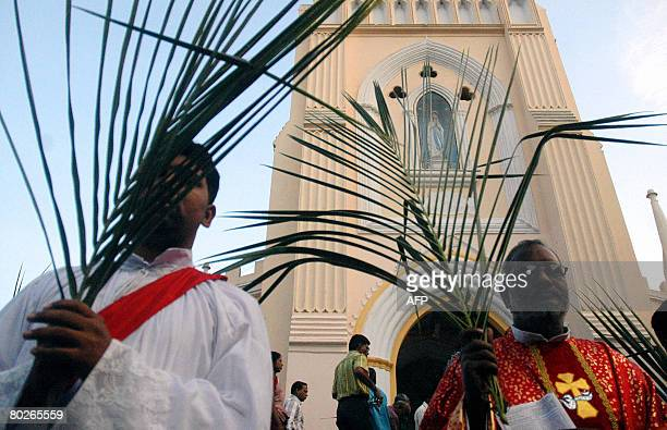 An Indian Roman Catholic church Parish Priest holds palm leaves ahead of a mass at St Mary's Church in Secunderabad the twin city of Hyderabad on...