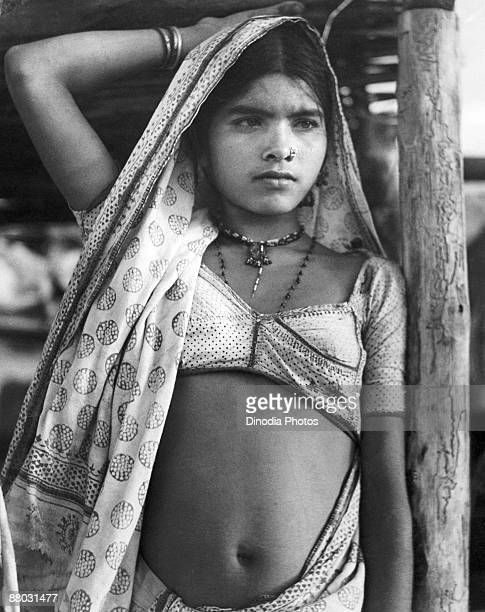 An Indian rural girl wearing a saree and blouse in a rural area of Rajasthan India 1940s