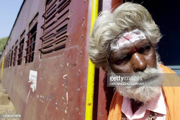 An Indian sadhu looks out from a train compartment as he arrives at the railway station in Kumbakonam, around 275 Kms south-west of Madras, 05 March...