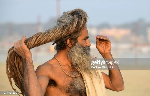 An Indian sadhu of Digamber Akhada adjusts his dreadlocks during the land allotment of the Kumbh Mela festival, on the bank of the Gange river in...