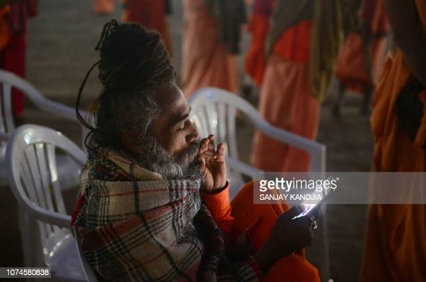 An Indian sadhu of Juna Akhada uses his smartphone after a Dharam Dhwaja ceremony flag hosting ceremony at the Sangam area ahead of the upcoming...