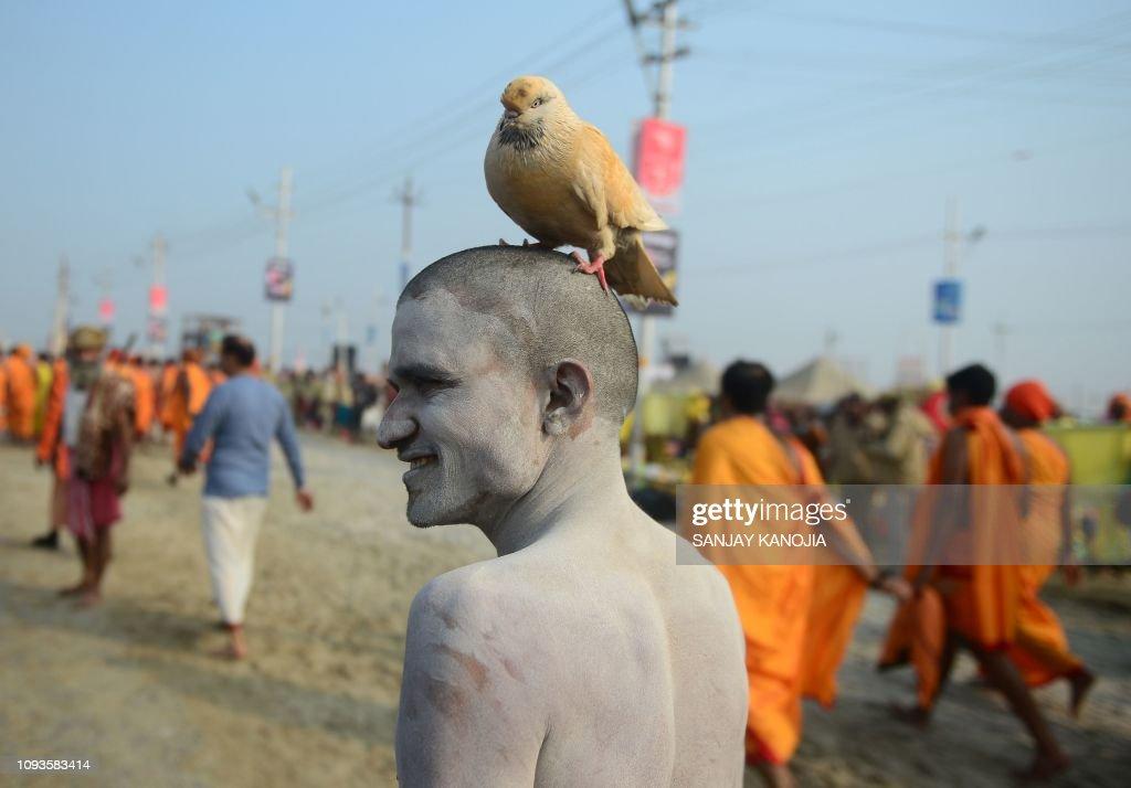 an-indian-sadhu-stands-with-a-bird-on-hi