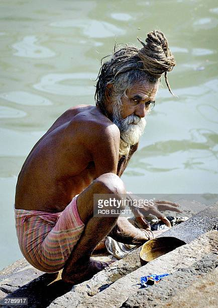 An Indian Sadhu with his matted hair wound into a knot on the top of his head stops off to do his washing on the steps near the Gateway to India in...