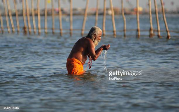 An indian sadhu worships during bath on the banks of holy sangam confluence of Ganges Yamuna and mythical Saraswati rivers on ocassion of Maghi...