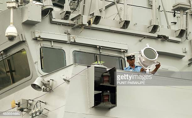 An Indian sailor adjusts a bridge wing search light on the new Indian Naval ship Kolkata anchored at the navy dock during its media preview in Mumbai...