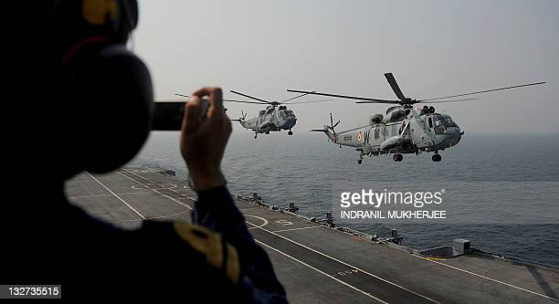 An Indian sailor takes a photograph on his mobile phone of Sea King helicopters preparing to land on board Indian Navy's aircraft carrier INS Viraat...