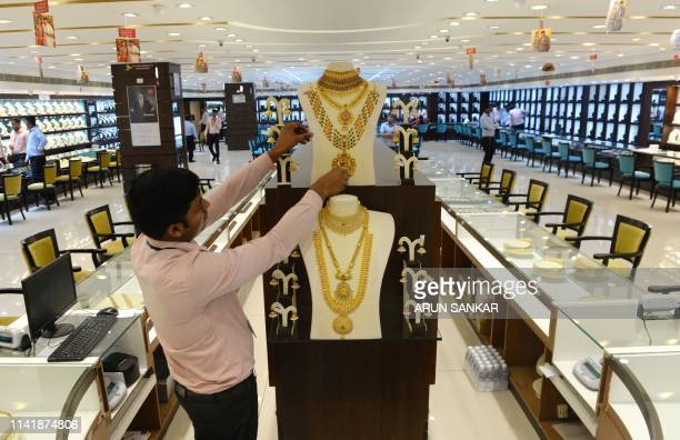 An Indian sales assistant arranges gold ornaments during the Hindu festival of Akshaya Tritiya at a jewellery shop in Chennai on May 7 2019 Akshaya...