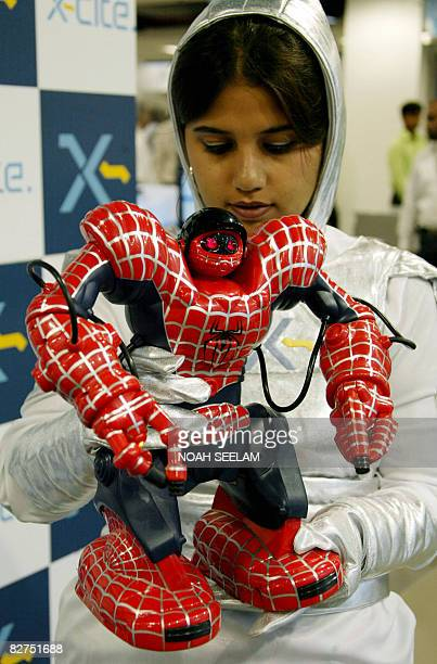 An Indian sales girl poses with robots at a press conference in Hyderabad on September 10 2008 for the launch of Impact retail's consumer electronics...