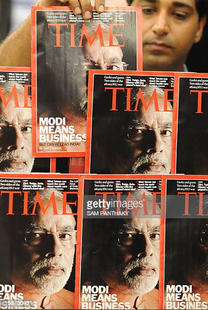 An Indian salesman arranges copies of Time magazine featuring a cover photo of Gujarat Chief Minister Narendra Modi at a store in Ahmedabad on March...
