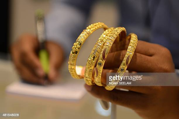 An Indian salesperson calculates the price of gold bracelets at a jewellers in Hyderabad on July 22 2015 Gold fell by INR 108 to trade at INR 24689...