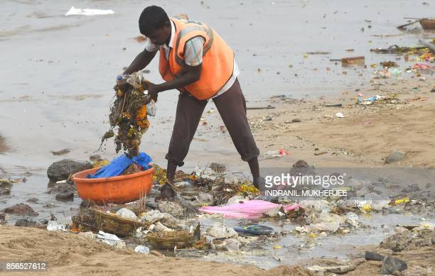 An Indian sanitation worker cleans Juhu beach of trash on the third anniversary of the launch of the Swachh Bharat Abhiyan cleanliness campaign in...