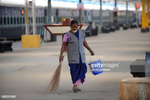 An Indian sanitation worker cleans platforms at a train station in Chennai on February 1 2017 India is to halve the basic rate of income tax to five...
