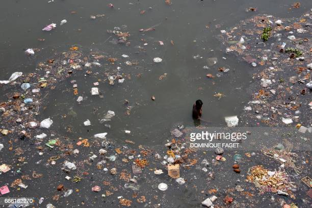TOPSHOT An Indian scavenger looks for recyclable items on the banks of the polluted Yamuna River on the outskirts of New Delhi on April 8 2017 Two of...