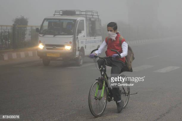 An Indian school boy cycles to school after three days off due to heavy smog in Amritsar on November 13 2017 Large swathes of north India and...