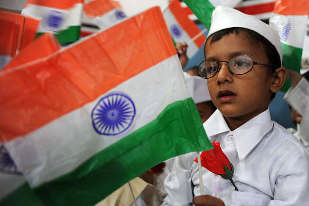 An Indian school boy dressed up as India`s first prime minister Jawaharlal Nehru waves the Indian national flag during celebrations for Children`s...