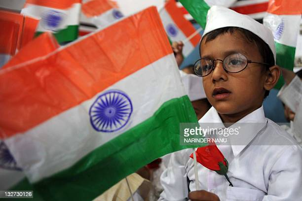 An Indian school boy dressed up as India's first prime minister Jawaharlal Nehru waves the Indian national flag during celebrations for Children's...