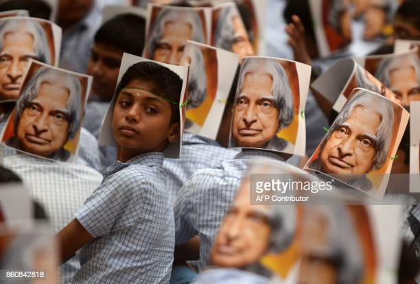 TOPSHOT An Indian school boy looks around as the children gather to make a portrait of the late former Indian president APJ Abdul Kalam to mark the...