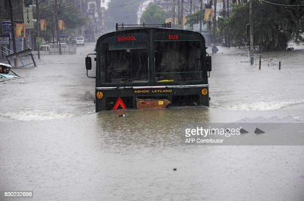 An Indian school bus drives through a flooded street during a heavy downpour in Agartala the capital of northeastern state of Tripura on August 11...