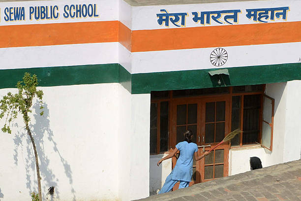 An Indian school girl dusts a school door in Amritsar on March 8 2013 Standards of education in rural areas in India are declining despite huge...