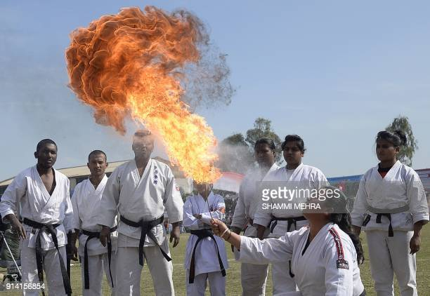 An Indian school girl performs fire breathing during the last day of Kila Raipur Games known as the rural Olympics at Kila Raipur on the outskirts of...
