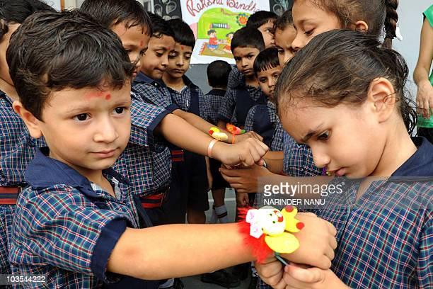 An Indian school girl ties a 'rakhi' onto the wrist of a school boy on the eve of the Hindu festival Raksha Bandhan at Sun Valley Public School in...