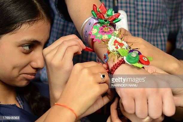 An Indian school girl ties a 'rakhi' sacred thread onto the wrist of a school boy on the eve of the Hindu festival Raksha Bandhan at a school in...