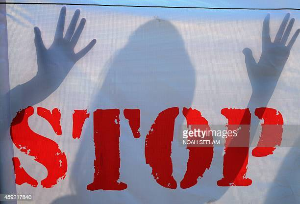 An Indian school student's shadow falls on a banner during an awareness Campaign against Child Sex Abuse in Hyderabad on November 19 the World Day...
