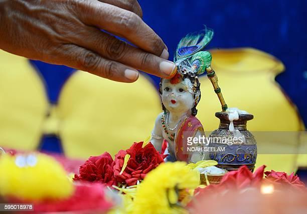 An Indian school teacher marks a statue of Hindu god, Lord Krishna with kumkuma on the occasion of Janamashthami, the birthday of Lord Krishna, in...