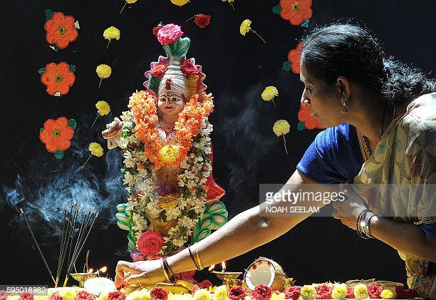 An Indian school teacher places a coconut as she offers prayers at a statue of Hindu god Lord Krishna on the occasion of Janamashthami, the birthday...