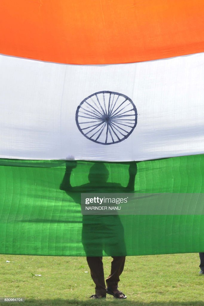 An Indian school worker holds an Indian national flag during a full dress rehearsal for the 70th Independence Day at Guru Nanak Stadium in Amritsar...