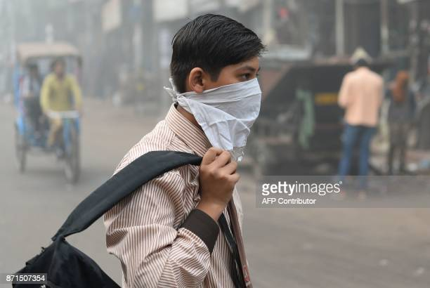 An Indian schoolboy covers his face with a handkerchief amid heavy smog in the old quarters of New Delhi on November 8 2017 Delhi shut all primary...