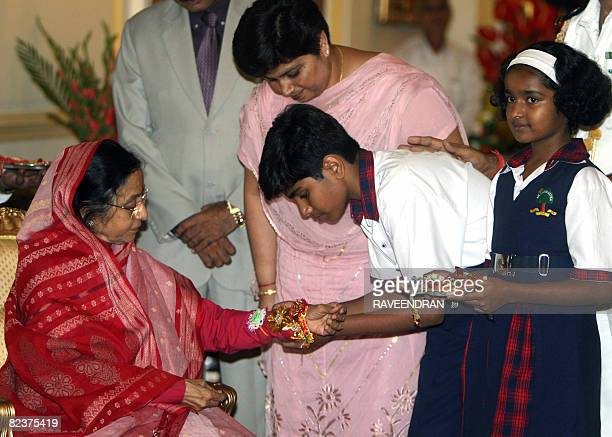 An Indian schoolboy ties a Rakhi or sacred thread around the wrist of Indian President Prathiba Singh Patil during a function marking the festival of...