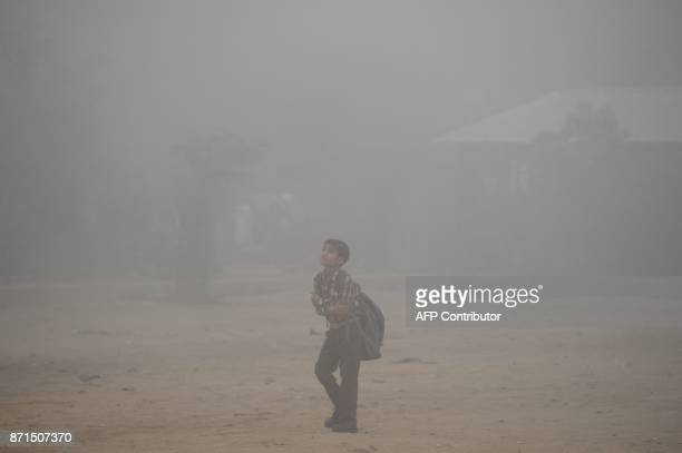 TOPSHOT An Indian schoolboy walks along a road amid heavy smog in the old quarters of New Delhi on November 8 2017 Delhi shut all primary schools on...